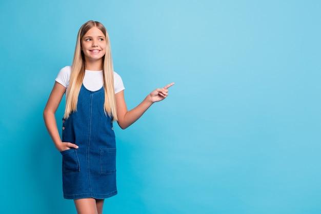 밝고 귀여운 금발 소녀의 전체 크기 사진은 파란색 배경에 격리된 흰색 티셔츠 데님 드레스를 입고 빈 공간을 보입니다.
