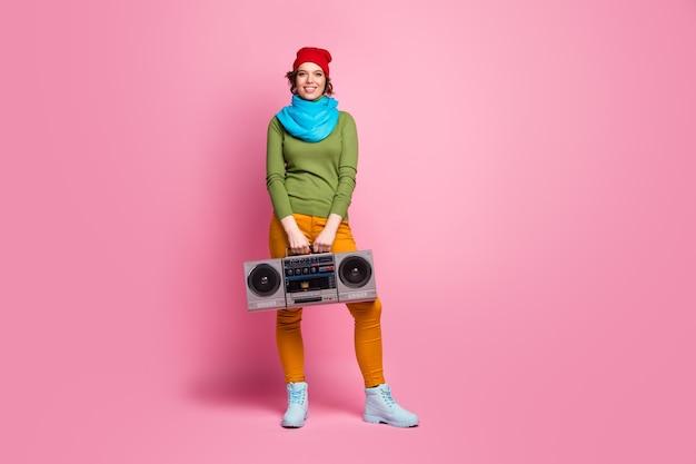 Полноразмерная фотография веселой мечтательной девушки, держащей бумбокс в ретро-ритме, наслаждается вечеринкой на выходных в сине-красной головной уборной обуви, изолированной над розовой стеной