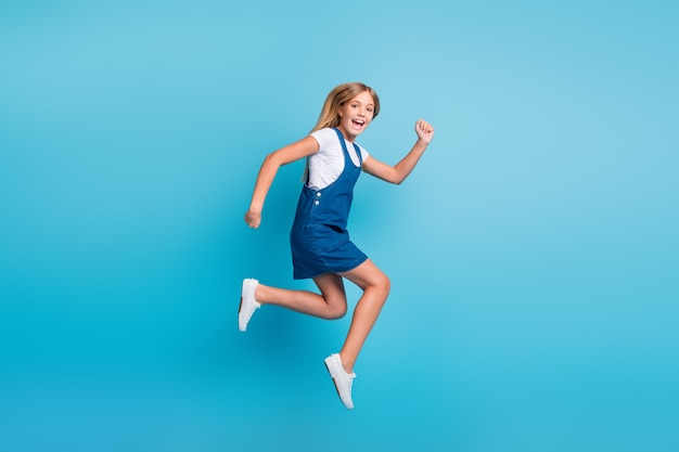 Полноразмерное фото веселой смешной блондинки, прыгающей на бегу, носить футболку, мини-платье, кроссовки, изолированное на пастельно-синем цветном фоне