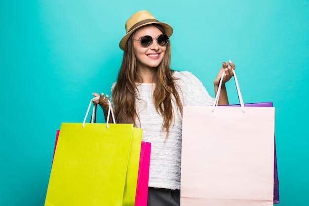 陽気な女の子のフルサイズの写真買い物に行く散歩を楽しむ春の自由な時間を楽しむ掘り出し物は多くのバッグを保持するピンクの一重項の靴を着用する孤立したパステルターコイズ色の背景