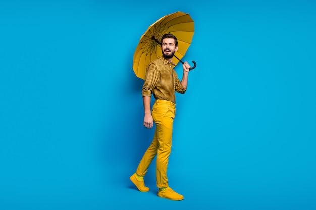 Полноразмерная фотография веселого парня, который наслаждается весенней дождливой погодой, держит яркий зонтик, хорошо выглядит, обувь copyspace, выделенная синим цветом