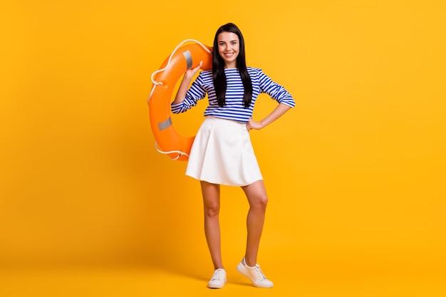 陽気なかわいい女の子の観光客のフルサイズの写真は、明るい輝きの色の背景の上に分離された青白い服を着てウォータースポーツスイムオーシャンホールドラバーライフブイをお楽しみください