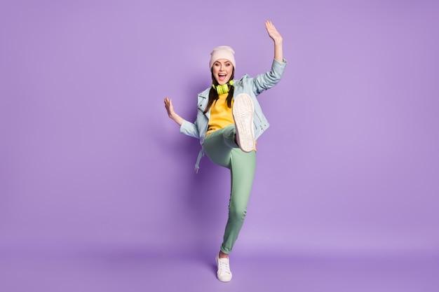 멋진 펑키 레이디 스트리트 옷 좋은 분위기 춤 이상한 젊은이의 전체 크기 사진은 다리를 높이 들고 캐주얼 모자 재킷 바지 신발 고립 된 보라색 배경