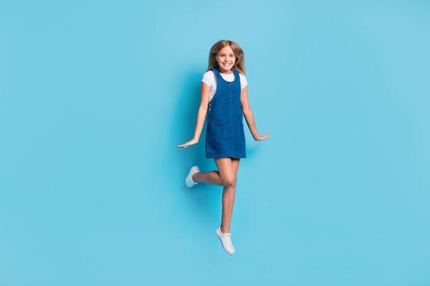 Полноразмерное фото крутой смешной девушки, прыгающей в белой футболке, джинсовой обуви, изолированной на пастельно-синем цветном фоне