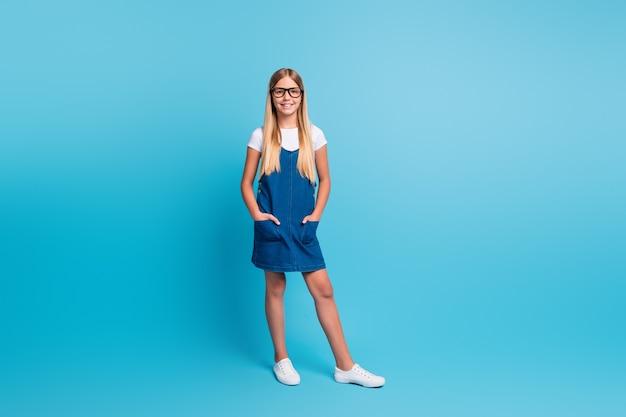 파스텔 블루 색상 배경에 격리된 티셔츠 드레스 신발을 신고 서 있는 멋진 학생 소녀의 전체 크기 사진
