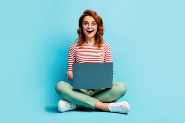 미친 놀란 여자의 전체 크기 사진 앉아 바닥 다리를 건너 작업 컴퓨터 검색 작업 웹 사이트 감동 비명 와우 세상에 파란색 위에 절연 세련된 복장 운동화를 착용
