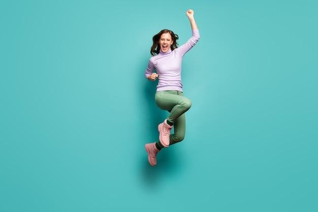 Полноразмерная фотография сумасшедшей красивой женщины, прыгающей высоко, праздновать открытие торгового центра продаж черную пятницу, поднять кулаки, носить фиолетовый джемпер, зеленые штаны, обувь, изолированные, чирок, пастельный цвет