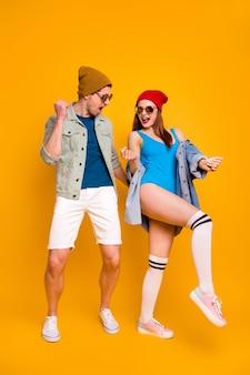 Полноразмерная фотография сумасшедших крутых двух современных людей, танцующих рок-н-ролл, вечеринка, одежда, рубашка, шорты, купальники, белые длинные носки, ноги, джинсовая куртка, джинсовая куртка, изолированный яркий цветной фон