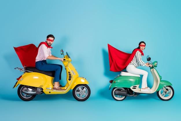 Полноразмерная фотография сумасшедшего возбужденного парня за рулем двух старинных мопедов в красной маске-накидке, мчащейся дорожной вечеринке, роль супергероев, пальто, летящая в воздухе, изолированная стена синего цвета