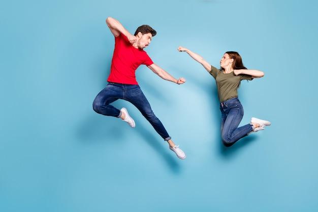 Полноразмерная фотография сумасшедшего мужчины два человека женщина мужчина супруги не согласны прыжок бой кикбоксинг носить зеленую красную футболку джинсовые джинсы кроссовки, изолированные на синем фоне