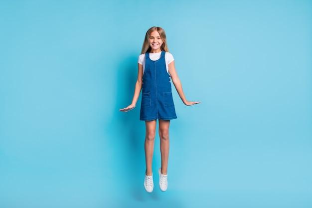 Полноразмерная фотография сумасшедшей позитивной блондинки, прыгающей в белой футболке, классической обуви, изолированной на пастельно-синем цветном фоне