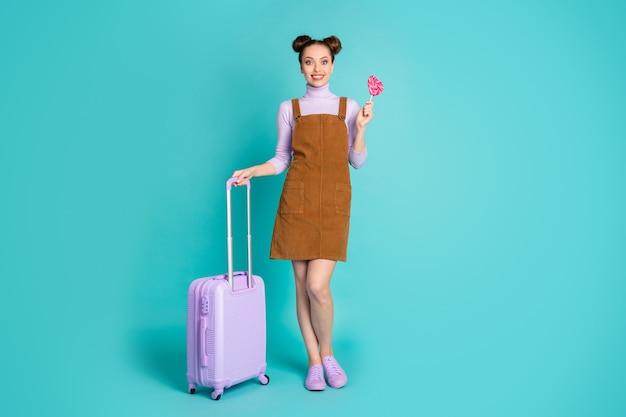 Полноразмерная фотография симпатичной привлекательной прически с верхним узлом, дамы, ожидания регистрации, возбужденных выходных за границей, оружия, сумок с конфетами, коричневого платья, фиолетового пуловера, кроссовок, изолированного бирюзового цвета