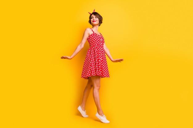 Полноразмерная фотография милой милой девушки иди, погуляй, смотри, copyspace, наслаждайся ее весенними каникулами, свободное время, расслабляйся, носи одежду в стиле ретро, белая обувь, изолированная на стене желтого цвета