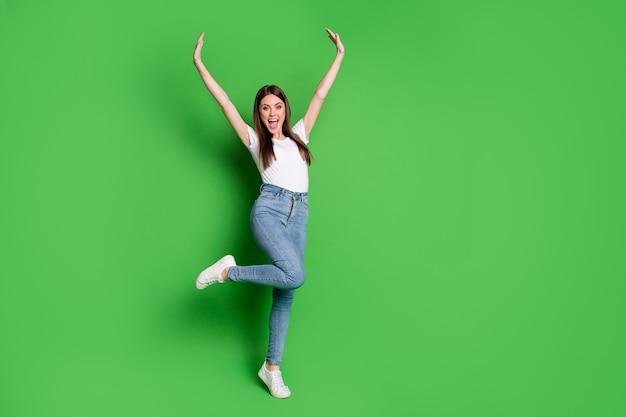 かわいい成功したブルネットの髪の若い女性のフルサイズの写真は、緑の背景に分離されたtシャツジーンズスニーカーを着て叫ぶ