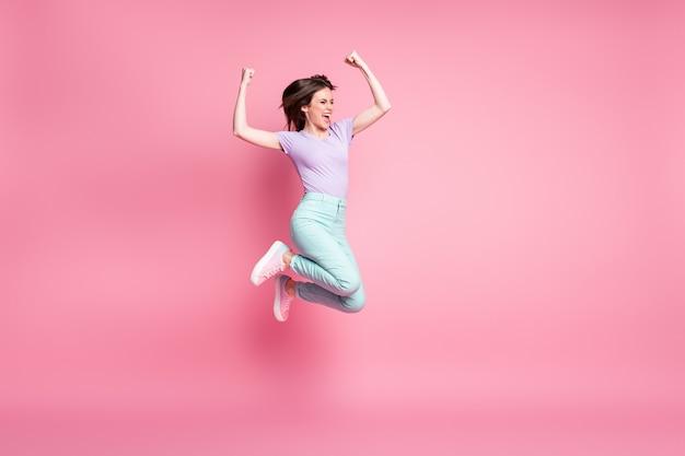 Полноразмерная фотография восхищенной сумасшедшей девушки прыгает, наслаждаясь лотереей, выигрывает, поднимает кулаки, кричит, носит бирюзовые фиолетовые брюки, кроссовки, изолированные на пастельном цветном фоне
