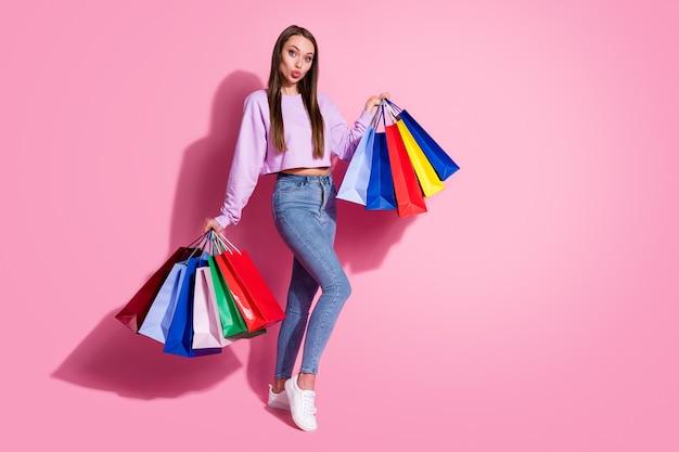 夢のような軽薄な女の子のショッピングセンターのクライアントのフルサイズの写真は、パステルカラーの背景の上に分離されたエアキスウェアライラックスタイルのスタイリッシュなトレンディなジャンパーデニムジーンズを送信します