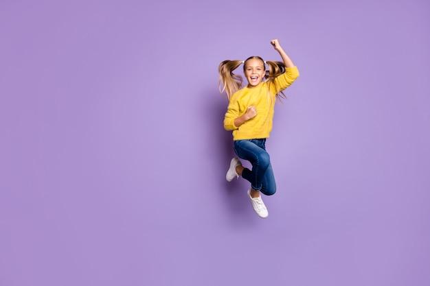 Полноразмерная фотография восторженного ребенка, прыгающего, выигравшего в лотерею, поднимает кулаки, кричит, да, носите одежду в повседневном стиле, изолированную над стеной фиолетового цвета