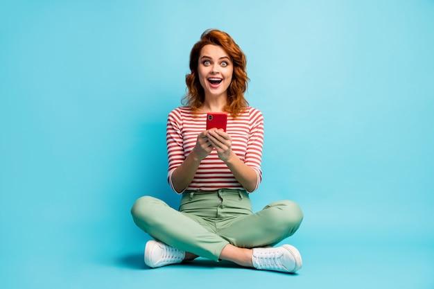 Полноразмерная фотография восторженной изумленной девушки сидит, скрестив ноги, использует мобильный телефон, читает новости социальных сетей, впечатлен крик, вау, боже, носить зеленые белые туфли, изолированные на синем цвете