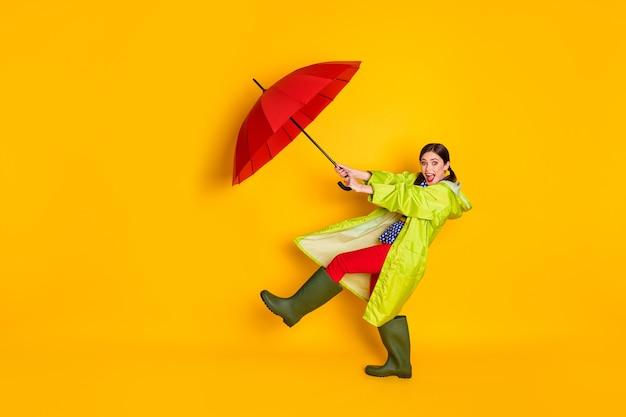 Полноразмерная фотография возбужденной сумасшедшей девушки, удерживающей ловушку, воздушную лету, дуновение ветра, зонтик, носить синюю пунктирную блузку, резинки, изолированные на ярком блестящем цветном фоне