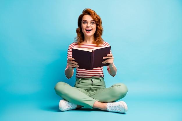 興奮した狂気の女性オタクのフルサイズの写真は、床の足を交差させて読んだ本を読んで、物語の悲鳴に感銘を受けました。