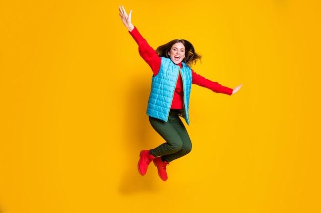 흥분한 소녀 점프의 전체 크기 사진은 비행 비행기가 밝은 광택 배경 위에 격리된 부주의한 부주의한 착용 빨간 스웨터 부츠를 상상하는 것을 상상합니다.