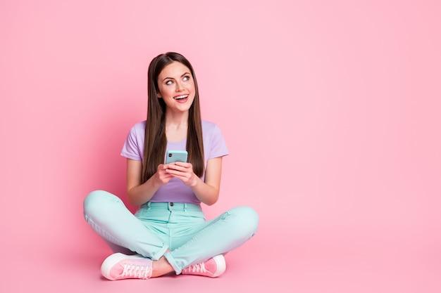 Полноразмерная фотография взволнованной девушки сидит на полу, скрестив ноги, пользуется мобильным телефоном, набирает текстовые сообщения, набирает отзывы в социальной сети, носит бирюзовые фиолетовые фиолетовые брюки, изолированные на пастельном цветном фоне