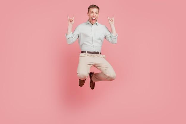 興奮した男の幸せなポジティブな笑顔のフルサイズの写真は、ピンク色の背景に分離されたロックホーンサイン残忍な金属の恋人を示しています