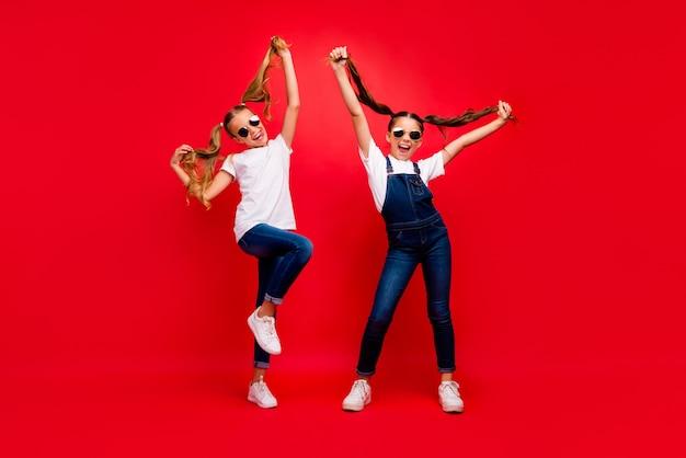 Полноразмерная фотография фанк-сумасшедших подружек стоит отдохнуть расслабиться на летних каникулах крик крик держать косички носить современную одежду белые кроссовки изолированный красный цвет фона