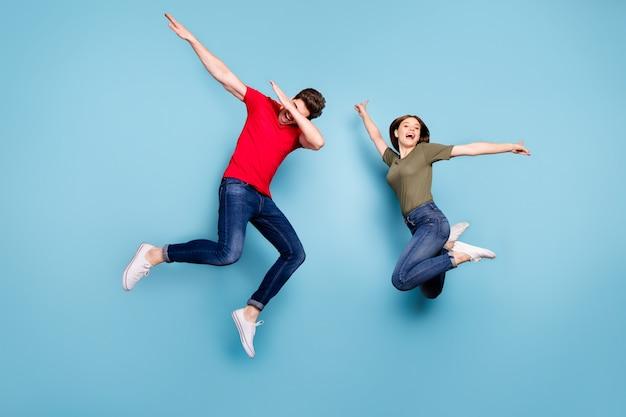 Полноразмерная фотография фанк-сумасшедших двух женатых людей, студентов, весело прыгающих, мужчина, танцоры, танцоры, женщина, поднимающая руки, носит зеленую красную футболку, джинсовые джинсы, кроссовки, изолированный синий цвет фона