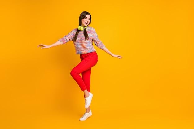 Полноразмерная фотография фанк-мечтательной девушки наслаждается слушать музыку в гарнитуре танцор танцует в клубах на дискотеке носить хорошо выглядящие туфли-свитера, изолированные на фоне сияющего