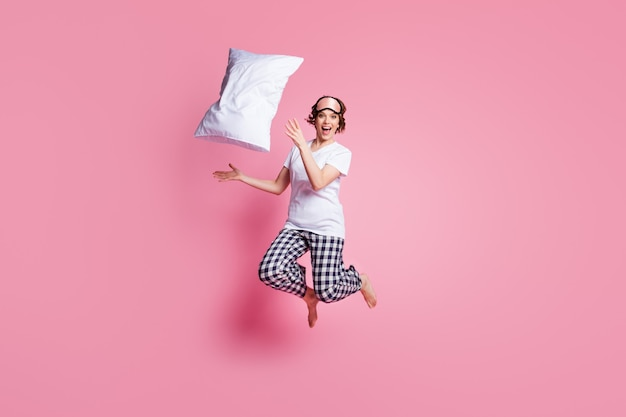 Полноразмерная фотография смешной дамы, прыгающей в высоту, бросает подушку на розовую стену