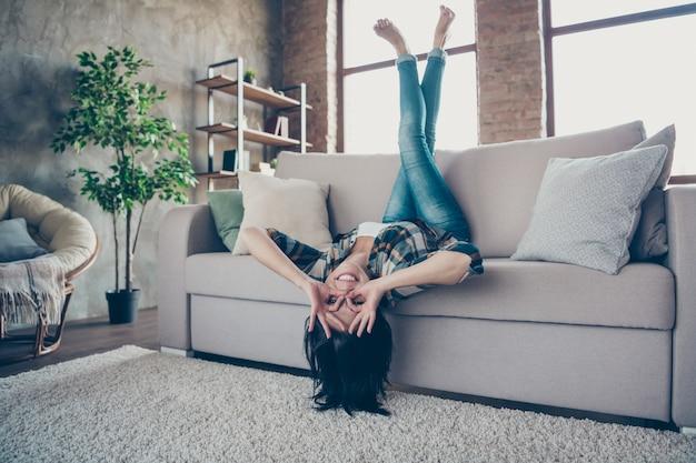 재미있는 여자의 전체 크기 사진 기뻐하는 다리를 거꾸로 들고 눈 사양 모양 거짓말 소파 착용 캐주얼 옷 아파트 실내 근처에 좋아요 기호를 보여주는