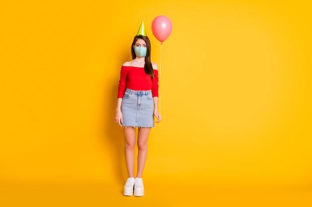 医療マスクの女の子のフルサイズの写真社会的な距離の傾向は、誕生日だけを祝う明るい輝きの色の背景の上に分離されたバルーンウェア赤いトップデニムスカート脚スニーカーを保持します