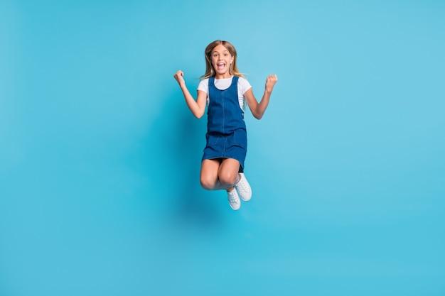 Полноразмерная фотография ура крутой девушки прыгает, носить футболку, туфли, изолированные на пастельно-синем цветном фоне