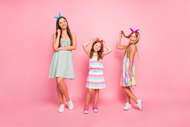 ピンクの背景で隔離のカラフルなドレススカートを着てポーズをとって明るいヘッドバンドを持つ素敵な女の子のフルサイズの写真