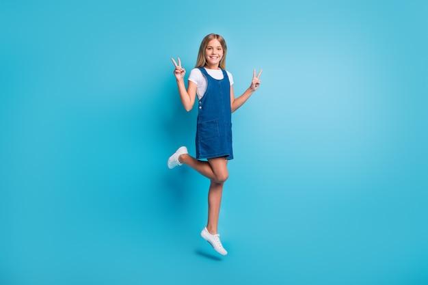 Полноразмерная фотография симпатичной крутой девушки, прыгающей на шоу, v-sign носить футболку, туфли, изолированные на пастельно-синем цветном фоне
