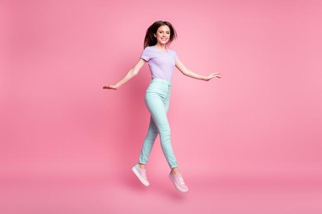Полноразмерная фотография красивой милой милой красивой девушки прыгает, наслаждаясь весенними выходными, надевает красивую одежду, обувь, изолированную на розовом цветном фоне