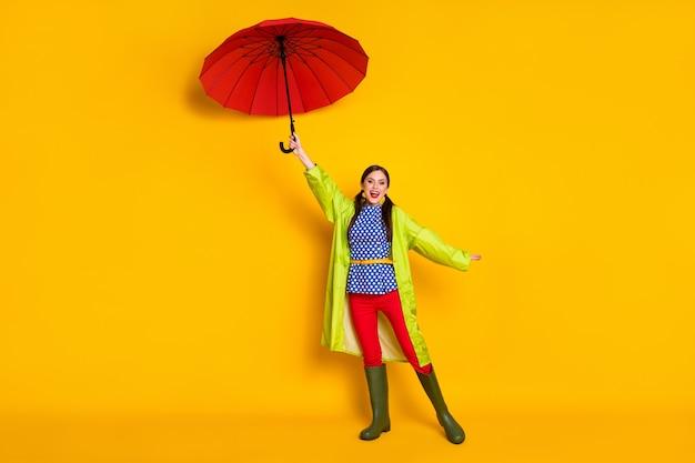 Полноразмерная фотография позитивной жизнерадостной девушки, держащей зонтик, воздушный ветер, дуть, летать, наслаждаться дождем, прогулка, носить хорошую одежду, синяя одежда, резинки, туфли, изолированные на ярком блестящем цветном фоне