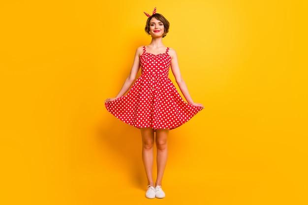 Полноразмерная фотография позитивной жизнерадостной девушки, прикоснувшейся к ее одежде в стиле пин-ап.