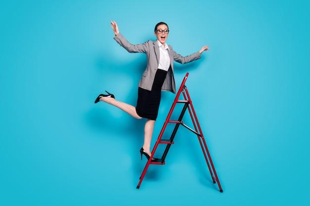 긍정적인 소녀 에이전트 스탠드 사다리의 전체 크기 사진은 블레이저 재킷 스커트 스틸레토 격리된 파란색 배경을 착용합니다