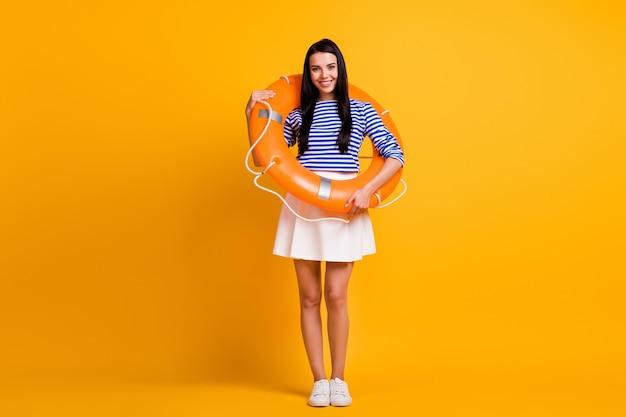 ポジティブな女の子のフルサイズの写真は、ウォーターリゾートの水泳を楽しむゴム製の膨脹可能な救命浮環を持っています明るい輝きの色の背景の上に分離された白い服の靴
