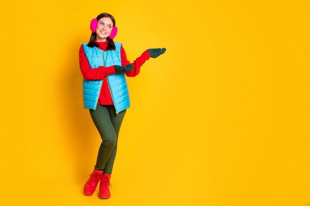 Полноразмерная фотография позитивной девушки, промоутера, руки, рукавицы, дисплей copyspace, предлагают рекламный объект, носить розовые свитера, сапоги, изолированные на ярком блестящем цветном фоне