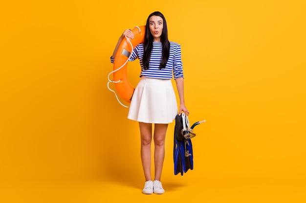 ポジティブな女の子の観光客のフルサイズの写真は、スキューバダイビングウォータースポーツホールドライフブイゴーグルマスクチューブ足ひれを着用青白いドレススカートシャツ孤立した明るい輝き色の背景をお楽しみください