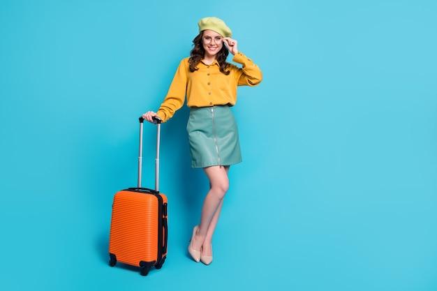 긍정적인 소녀 관광 준비 여행 여행 가방을 들고 있는 전체 크기 사진은 파란색 배경 위에 격리된 멋진 옷 모자를 쓰고 있습니다.