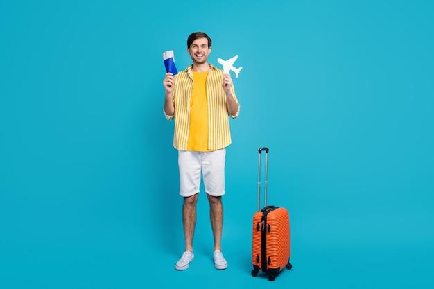 긍정적인 남자의 전체 크기 사진은 여행을 즐기는 종이 카드 비행기 체크인 확인을 위한 수하물이 파란색 배경에 격리된 멋진 복장을 하고 있습니다.