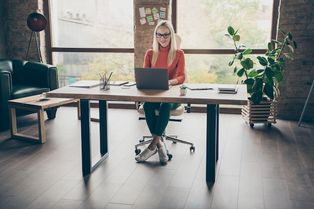 긍정적 인 여성 노동자 앉아 테이블의 전체 크기 사진 시작 전략 유형에 노트북 작업 사무실 로프트에 빨간색 터틀넥 착용