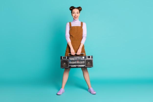 꽤 쾌활한 두 개의 빵 머리 여자 친구 밀레니엄 dj 재생 복고풍 음악 홀드 레코더 착용 가을 보라색 신발 스웨터 짧은 갈색 드레스 격리 된 청록색 배경의 전체 크기 사진