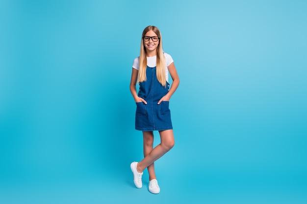 파스텔 블루 색상 배경에 격리된 티셔츠 드레스 운동화를 신고 서 있는 꽤 낙천적인 학생 소녀의 전체 크기 사진