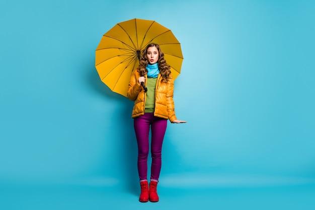 예쁜 여행자 아가씨의 전체 크기 사진 잡고 밝은 우산 화창한 계절 따뜻한 날 산책 거리 착용 노란색 외투 스카프 보라색 바지 빨간 신발 절연 파란색 벽