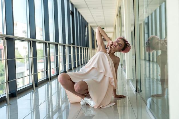 ピンクのドレスを着て廊下でポーズをとるロマンチックな女性のフルサイズの写真